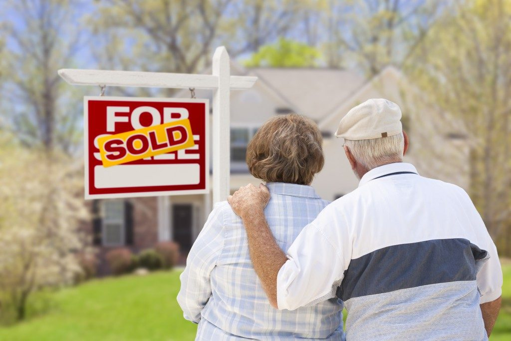 Senior Couple Hugging in Front of Sold Real Estate Sign