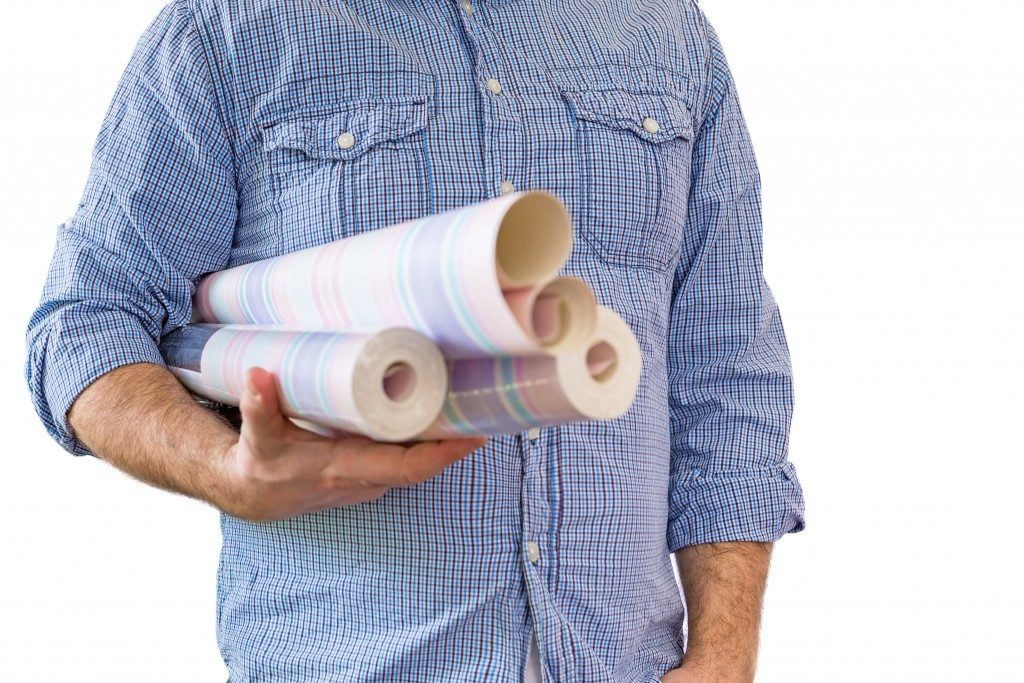 Man carrying rolls of wallpaper