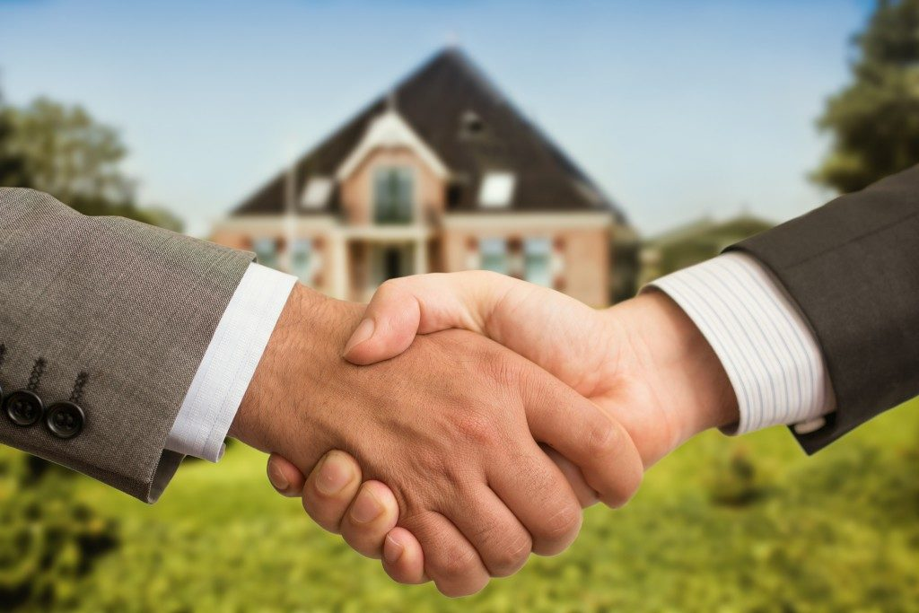 Photo of a handshake in front of a house