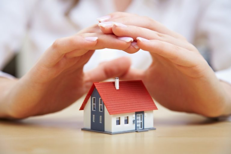 Woman hand placed above house model